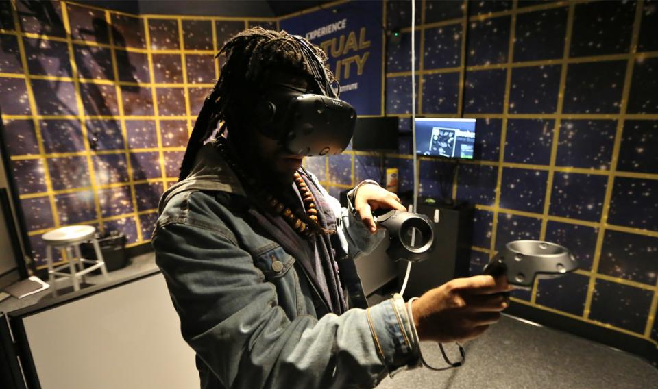 A guest experiencing virtual reality through a headset at the Holodeck exhibit at The Franklin Institute