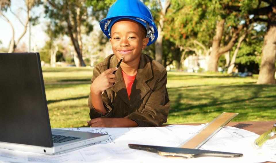 Image of a kid wearing a hardhat and holding a pencil at an outdoor table with a laptop, T-square and blueprints.