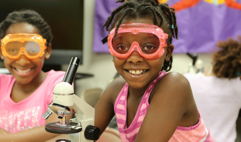Photograph of two girls in goggles and lab equipment looking through a microscope