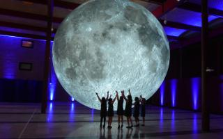 A group of people pose in front of a giant illuminated spherical model of Earth's Moon.