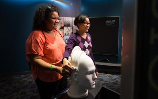 Two young adults using the visual pathway interactive in the Your Brain exhibit at The Franklin Institute.