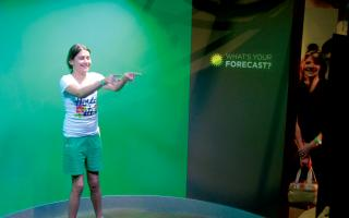Teenage girl recording her own weather forcast in Changing Earth at The Franklin Institute.