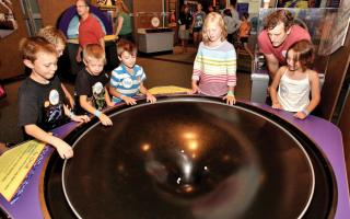 Children playing with the gravity well interactive at the Space Command exhibit at The Franklin Institute.