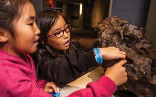 Two young girls touching the meteorite in the Space Command permanent exhibit at The Franklin Institute.