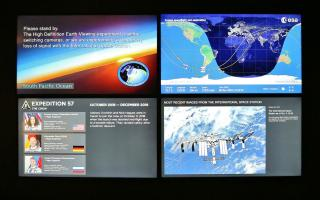 Four screens in the Space Command exhibit display live images from the International Space Station