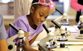 A young girl using a microscope during a Franklin Institute educational program.