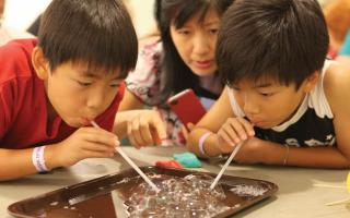 Two young boys blowing bubbles on a tray with their mother during a Member Sunday workshop.