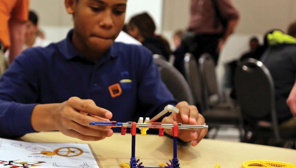 A teenage boy working with K'nex to engineer an example of a cam and gears.