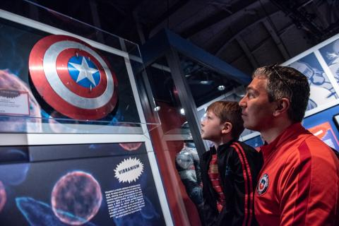 Photo of a child looking at a prop of Captain America's Shield